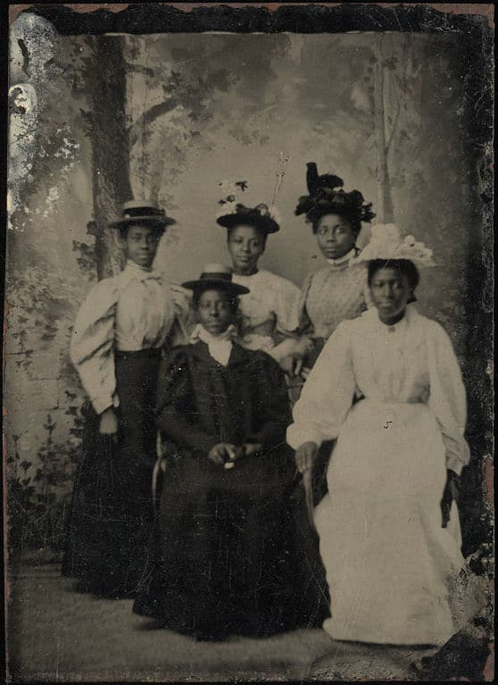 558px-Full_length_group_portrait;_five_young_ladies,_two_seated,_three_standing,_all_with_hats,_forest_backdrop._Tintype,_sixth_plate